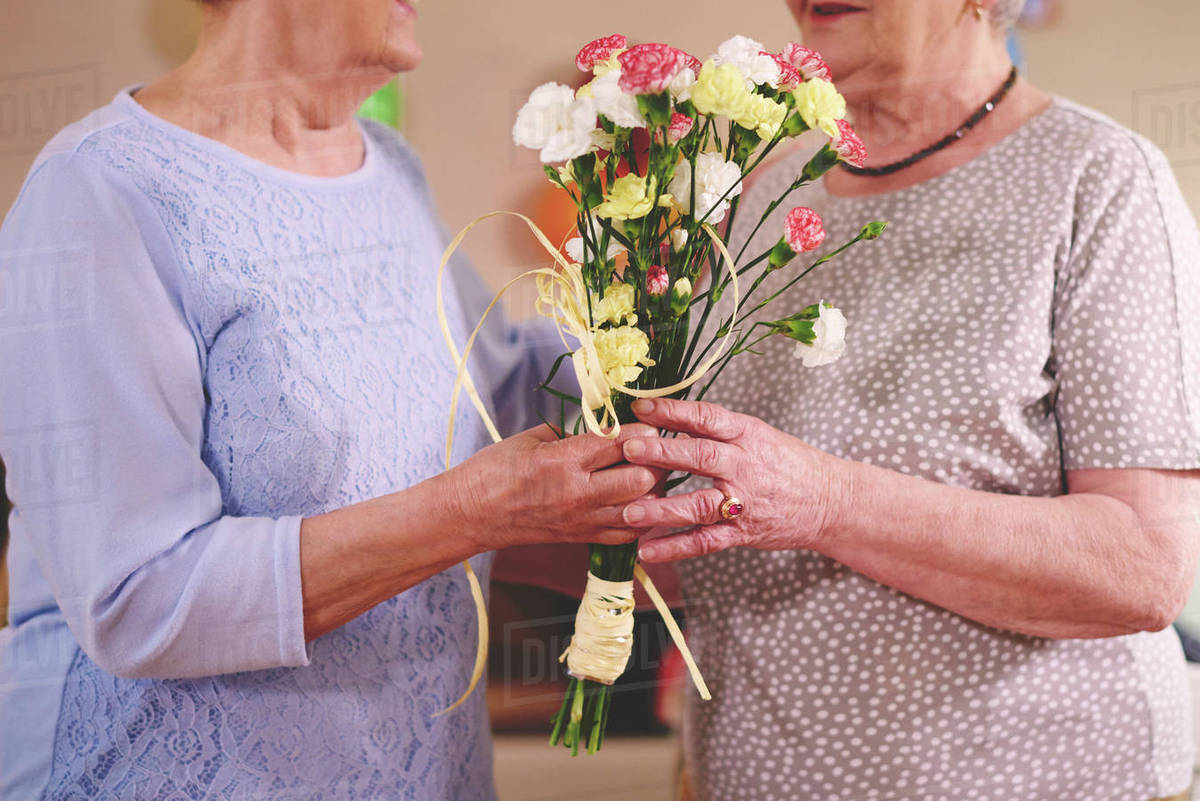 Senior Woman Giving Flowers To Friend At Birthday Party Stock