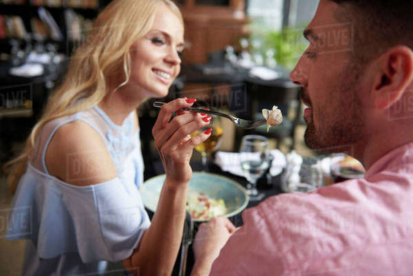 Young woman feeding boyfriend lunch at restaurant table Royalty-free stock photo