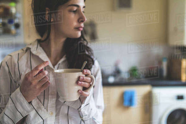 Young woman at home, wearing pyjamas, holding coffee cup Royalty-free stock photo