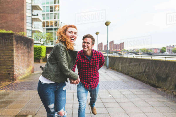 Couple outdoors, fooling around, running along street, laughing Royalty-free stock photo