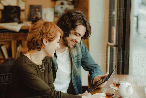 Young couple sitting in cafe, looking at digital tablet Royalty-free stock photo