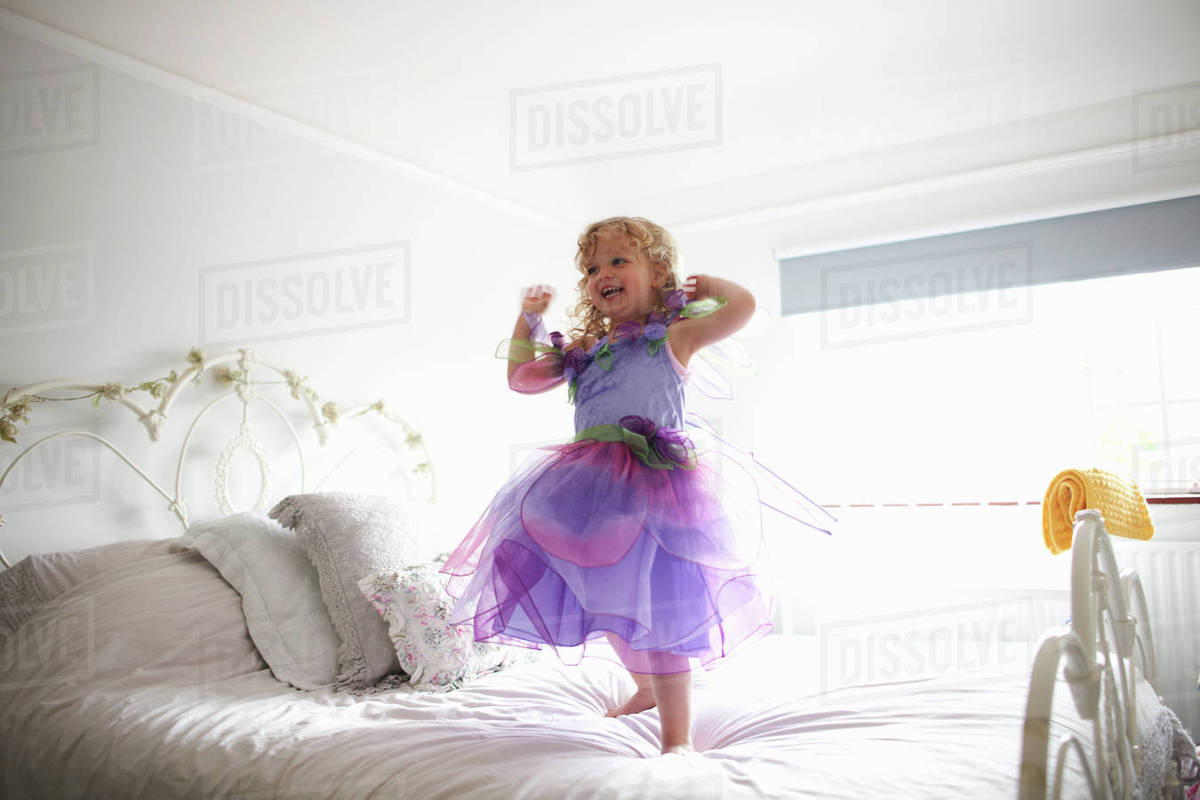 Young girl dressed in fairy costume, standing on bed, smiling Royalty-free stock photo