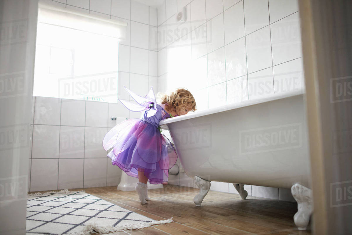 Young girl dressed in fairy costume, looking in bath tub Royalty-free stock photo