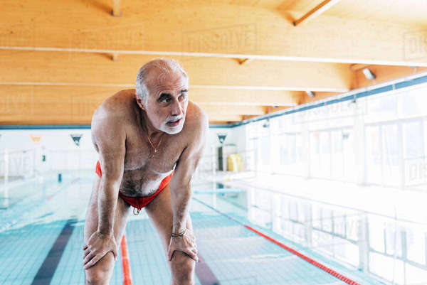 Senior man bending over catching his breathe by pool Royalty-free stock photo