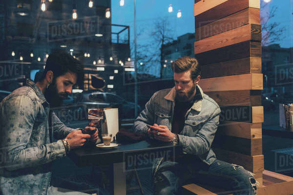 Two young male hipsters at sidewalk cafe looking at smartphones at night Royalty-free stock photo