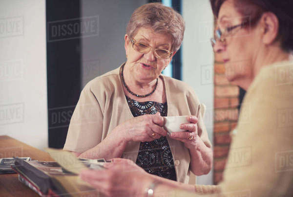 Two senior women looking at old photographs at table Royalty-free stock photo