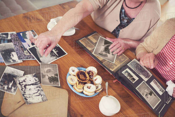 Overhead view of two senior women looking at old photographs at table Royalty-free stock photo