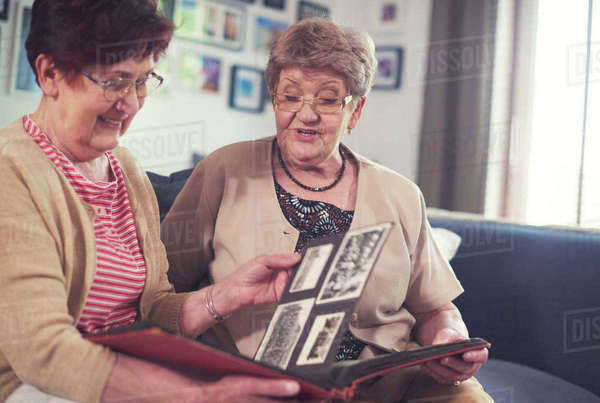 Two senior women on sofa looking at old photograph album Royalty-free stock photo