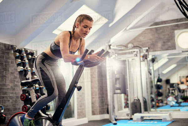 Young woman training, pedalling exercise bike in gym Royalty-free stock photo