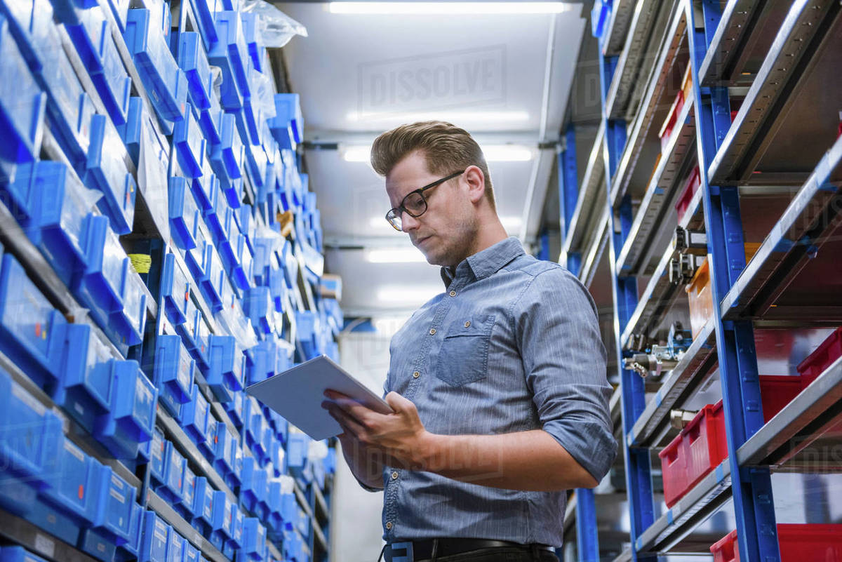 Manager using digital tablet for stock taking in factory warehouse stock  photo
