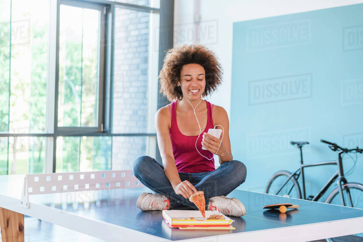 f6e4434e99 Young woman sitting on table tennis table listening to earphones and picking  up pizza