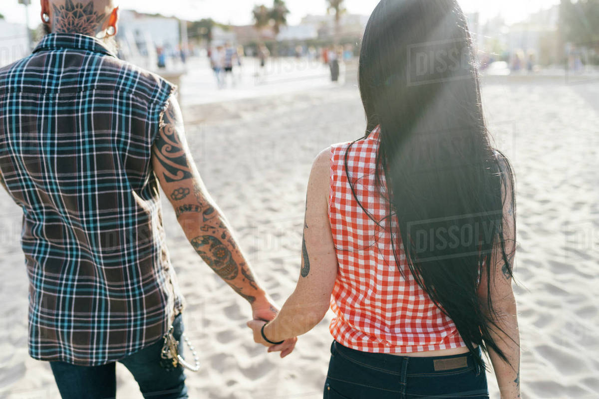 Mature tattooed hipster couple strolling on beach, rear view, Valencia,  Spain