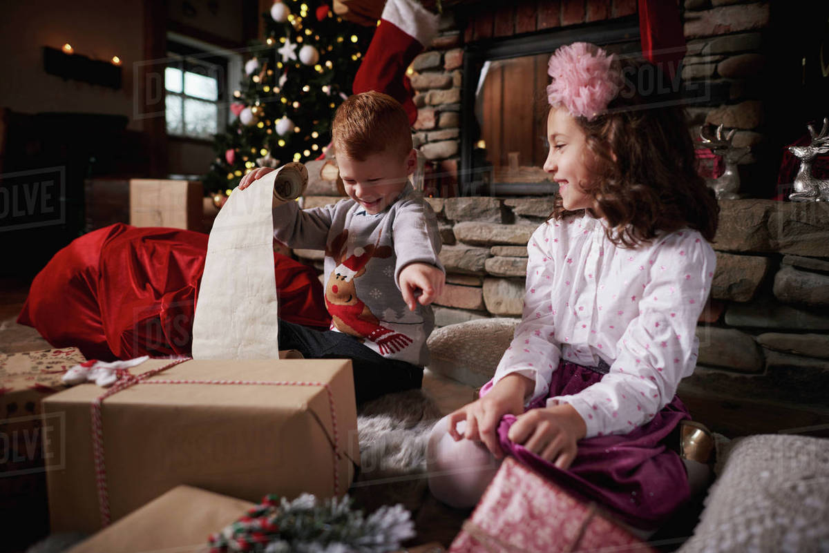 Young girl and boy sorting Christmas gifts, young boy rolling list ...