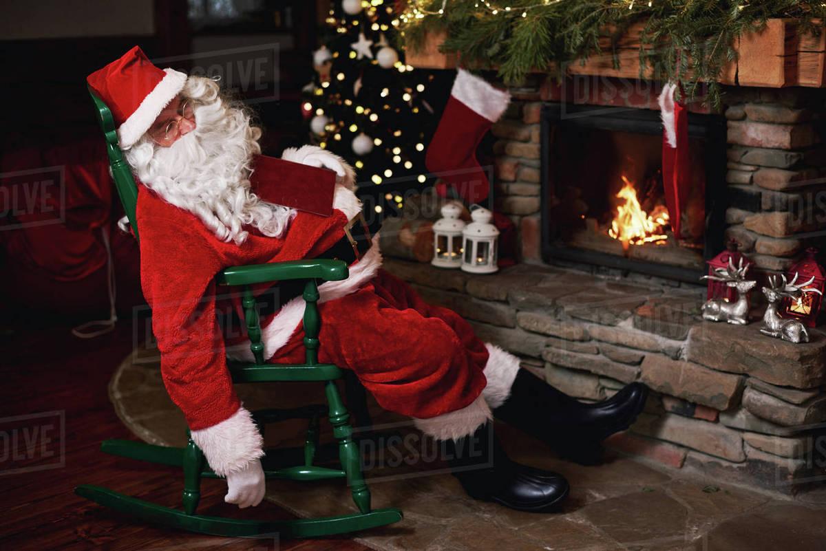 Santa Claus Sleeping In Chair Beside Fireplace Stock