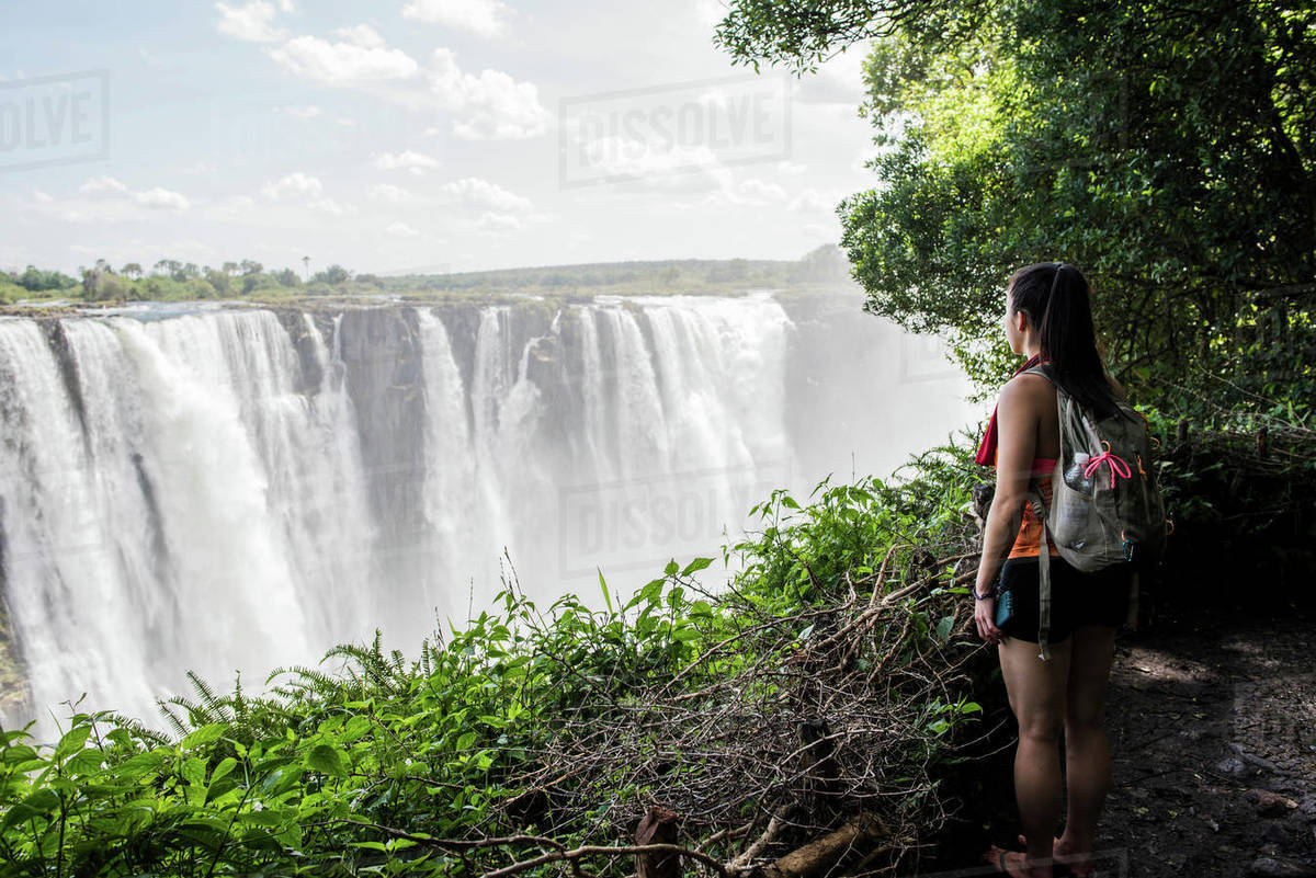 Young Female Tourist Looking Out At Victoria Falls Zimbabwe Africa D943 247 669