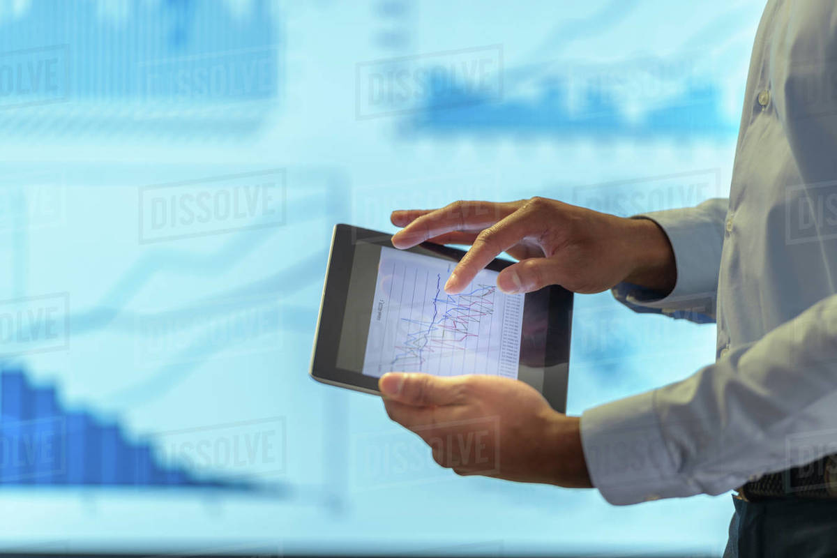 Man Using Business Digital Tablet During Presentation With Graphs And Charts Close Up Stock Photo