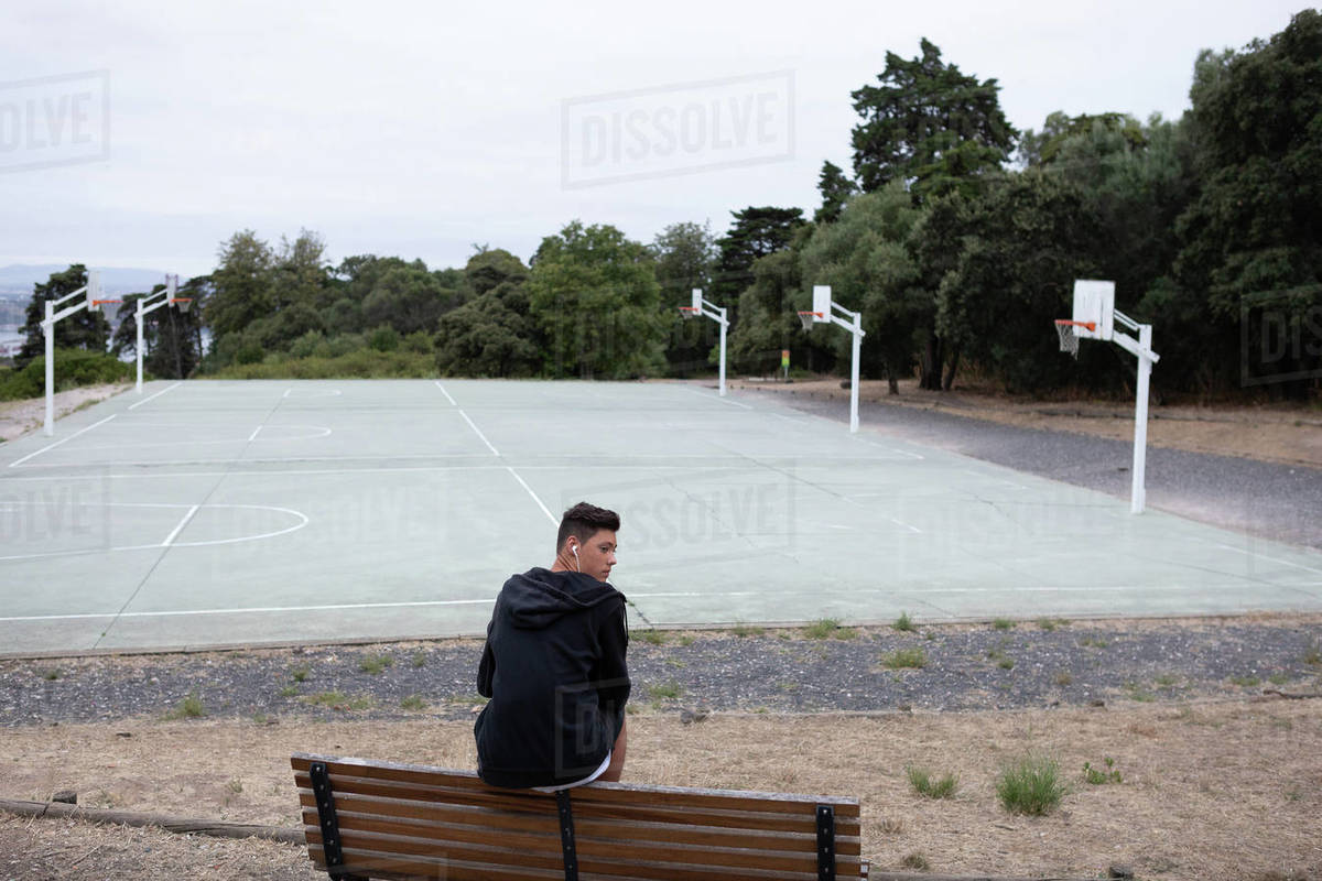 Male Teenage Basketball Player Looking Back From Park Bench By
