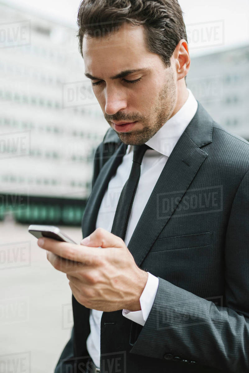 Mid adult businessman outside office building looking at smartphone, close up Royalty-free stock photo