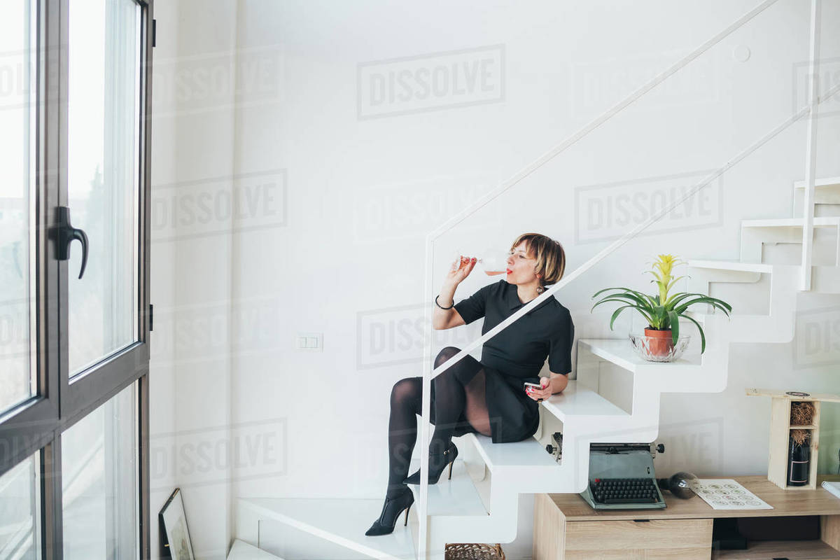 Woman drinking wine on staircase Royalty-free stock photo