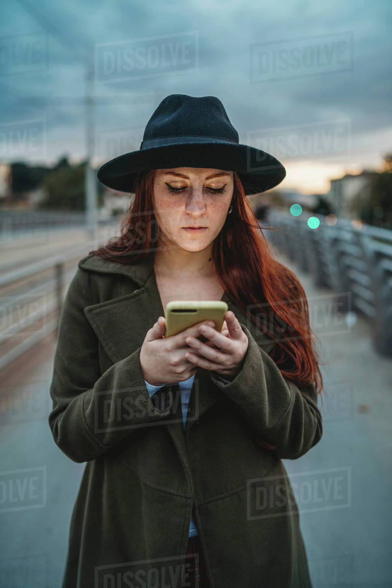 Young woman with long red hair on footbridge looking at smartphone at dusk Royalty-free stock photo