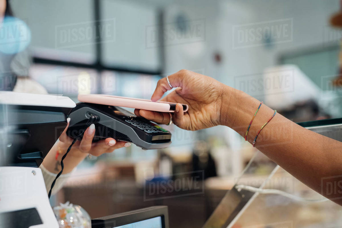 Young businesswoman making smartphone payment at cafe counter, cropped Royalty-free stock photo