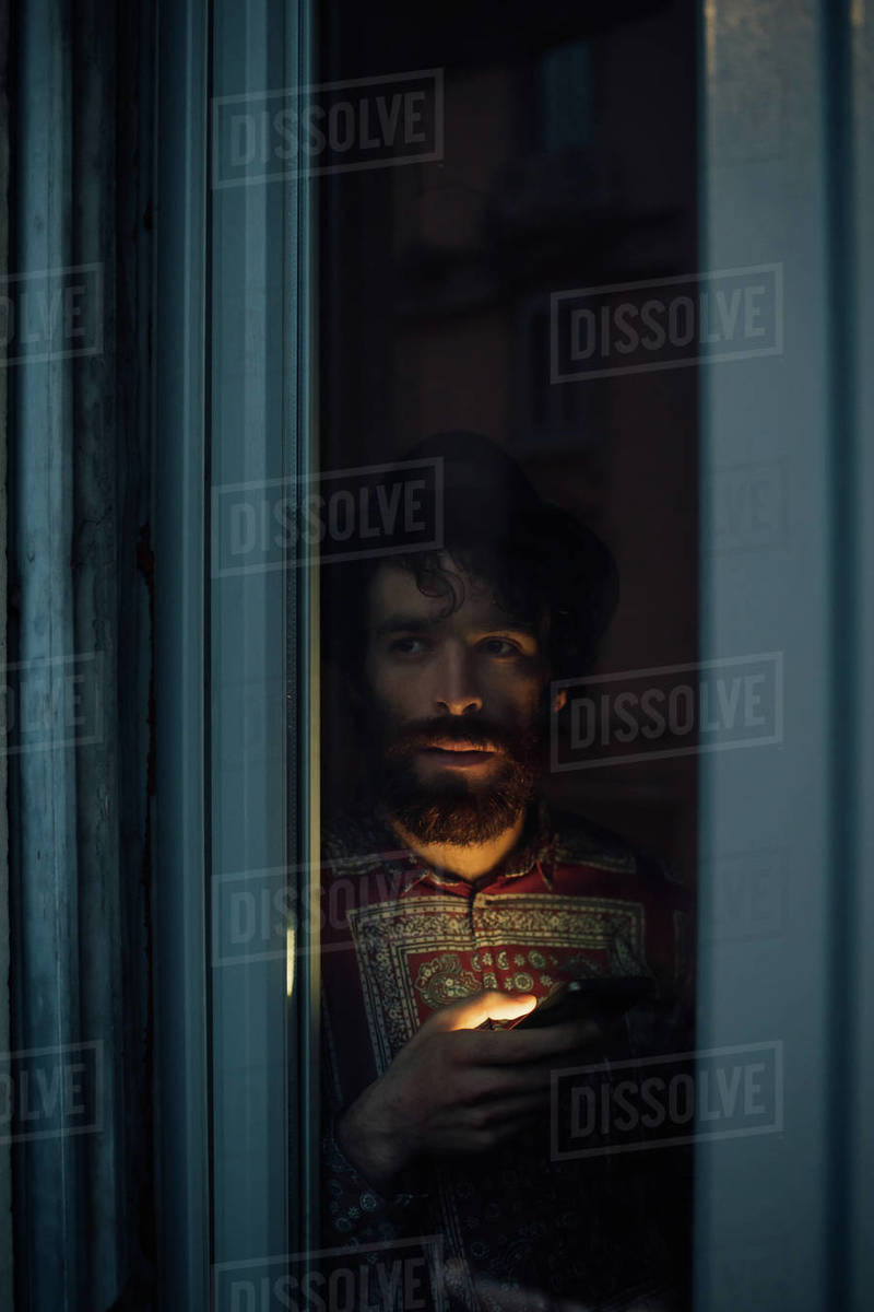 Bearded young man in deep thought by window Royalty-free stock photo