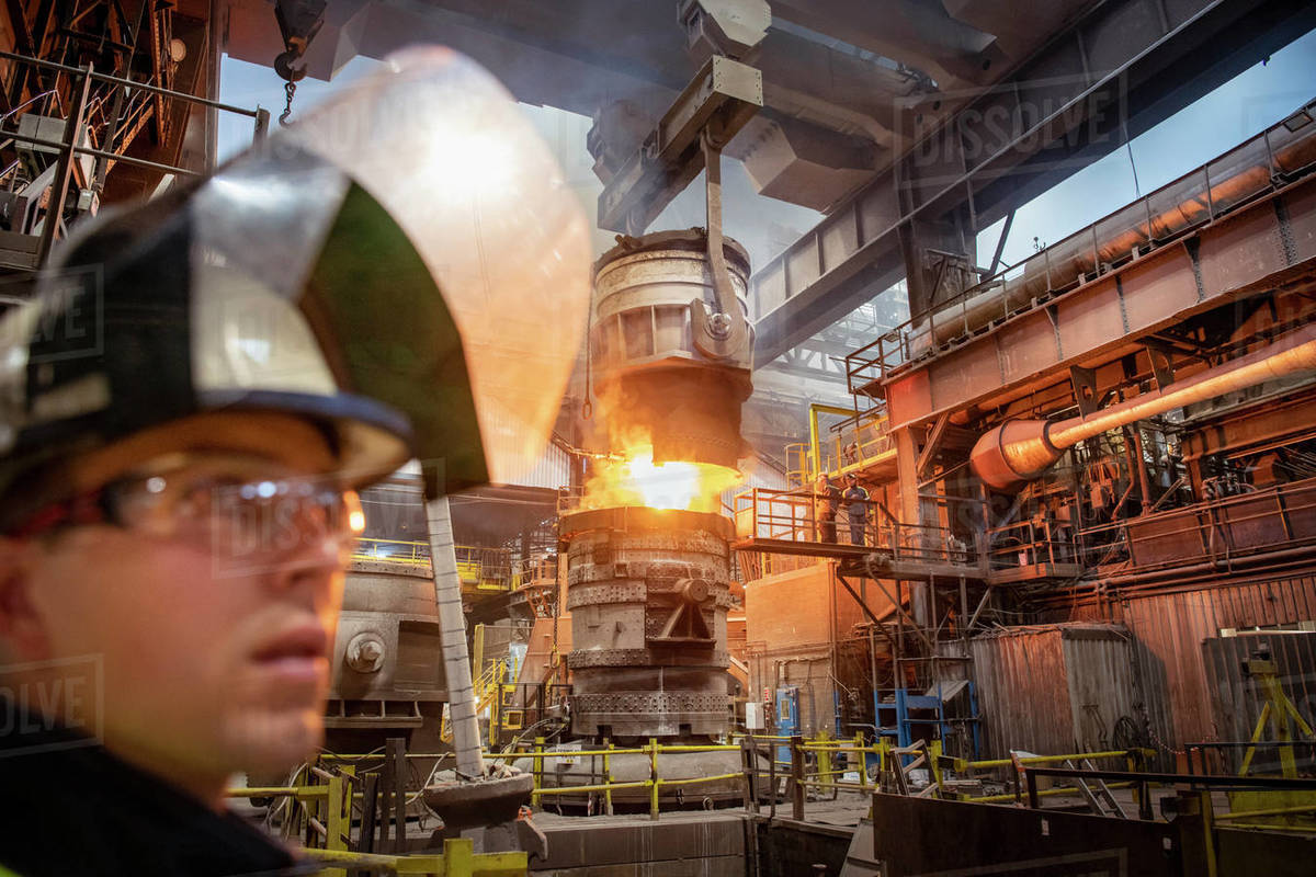 Apprentice steelworker in foreground during molten steel pour in steelworks Royalty-free stock photo