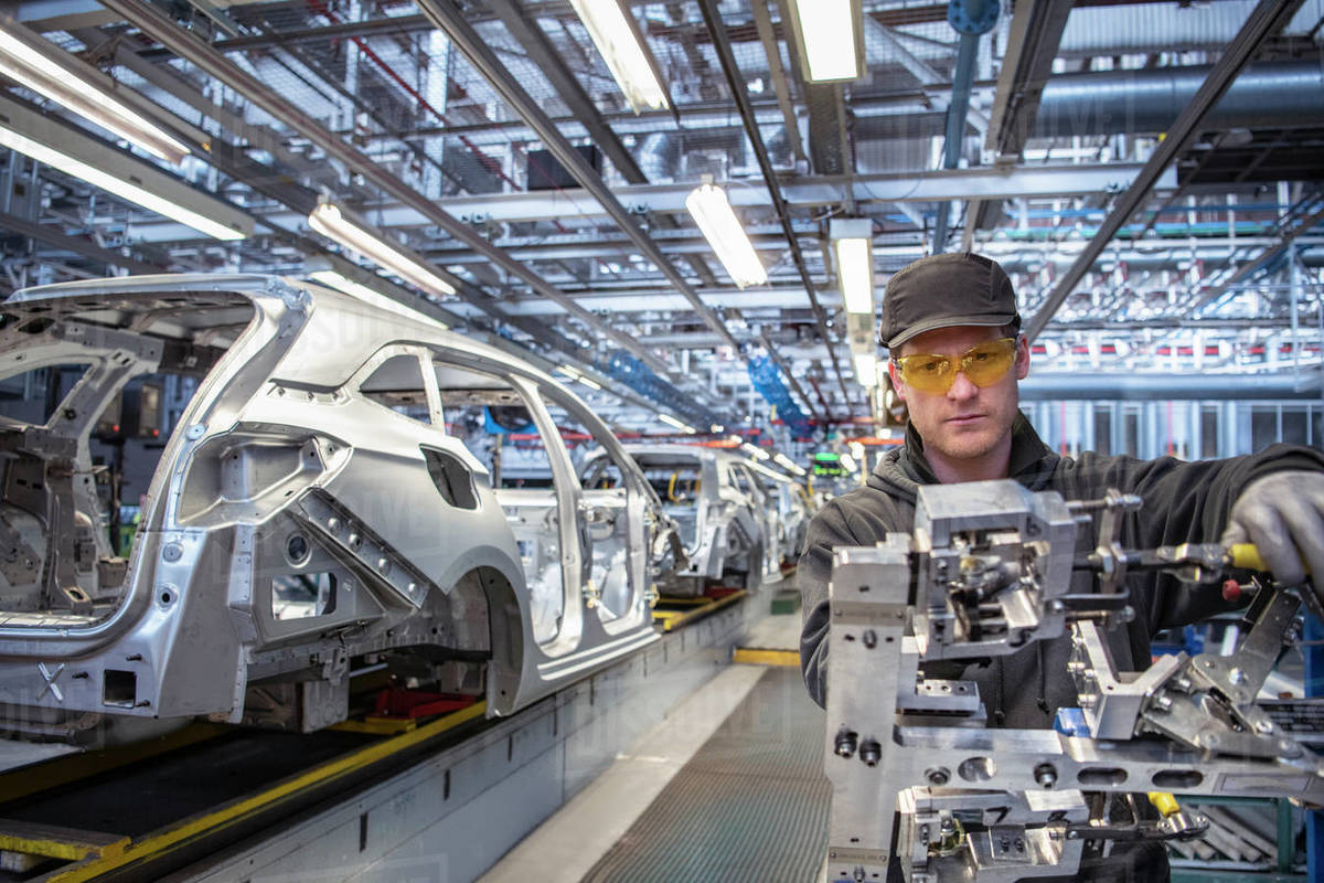 Car worker fitting parts on production line in car factory Royalty-free stock photo