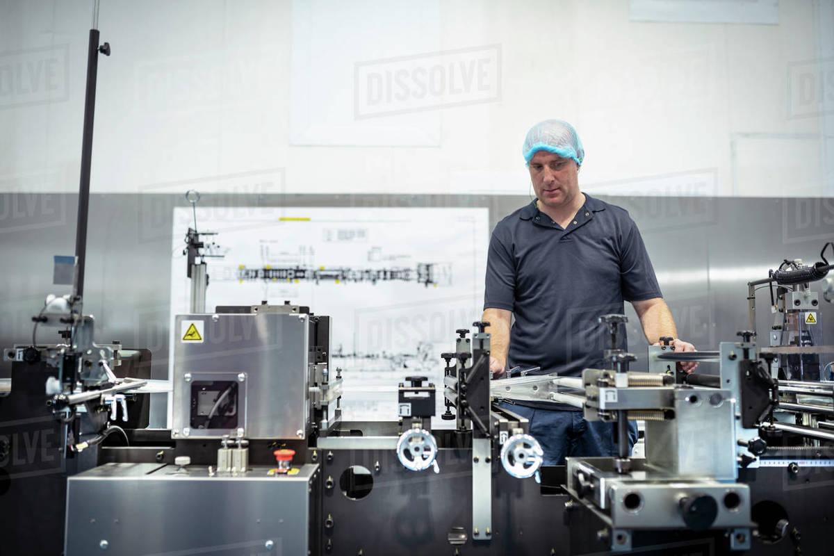 Worker adjusting printing machine in print factory Royalty-free stock photo