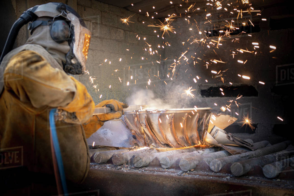 Worker cutting up scrap titanium aircraft parts in titanium recycling plant Royalty-free stock photo