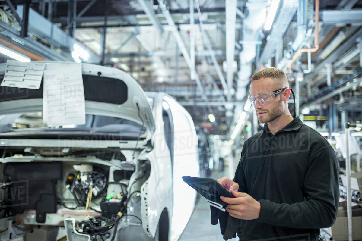 Engineer with digital tablet on production line in car factory Royalty-free stock photo