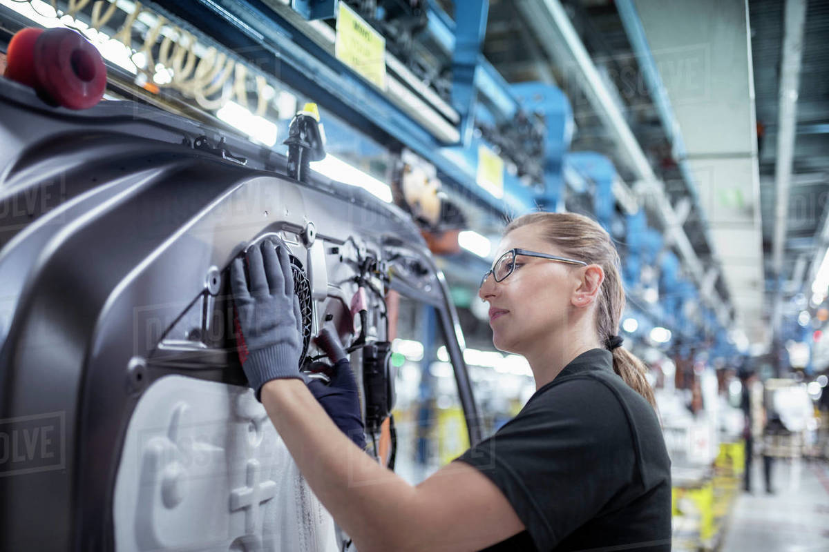Female worker assembling car doors on production line in a car factory Royalty-free stock photo