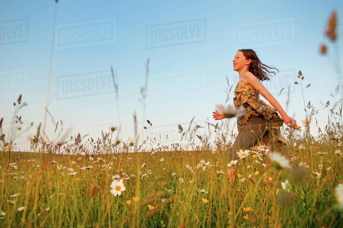 Girl running through wildflower meadow Royalty-free stock photo