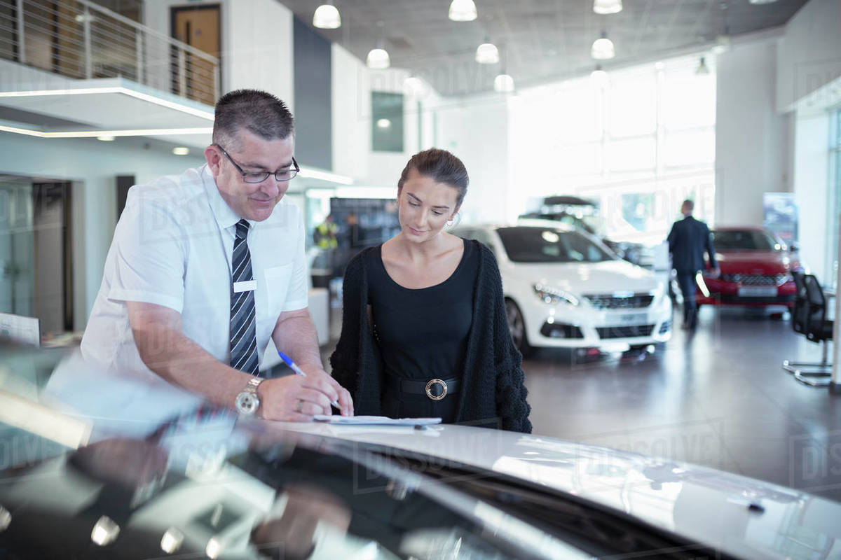 Salesman showing literature to customer in car dealership Royalty-free stock photo