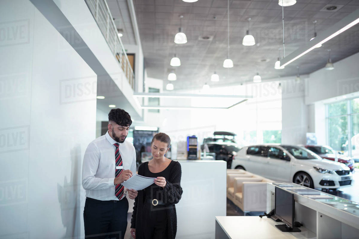 Salesman discussing contract with customer in car dealership Royalty-free stock photo