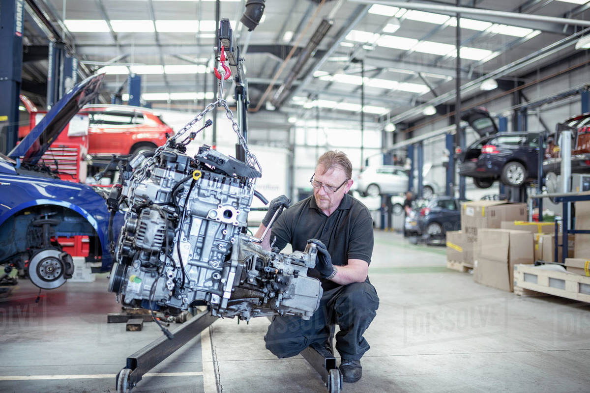 Engineer with car engine in car service centre Royalty-free stock photo