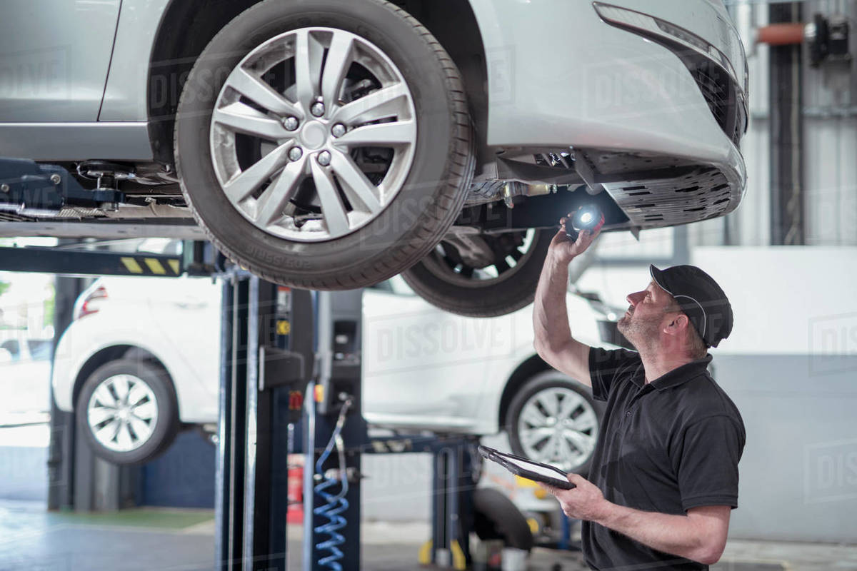 Engineer checking car on ramp in car service centre Royalty-free stock photo