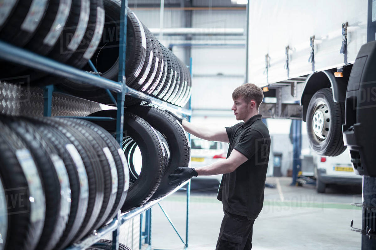 Apprentice engineer selecting tyres in car service centre Royalty-free stock photo