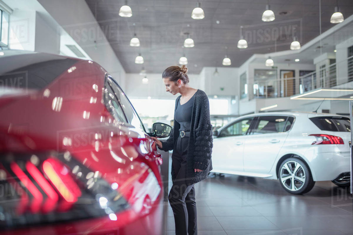 Female customer inspecting new car in car showroom Royalty-free stock photo