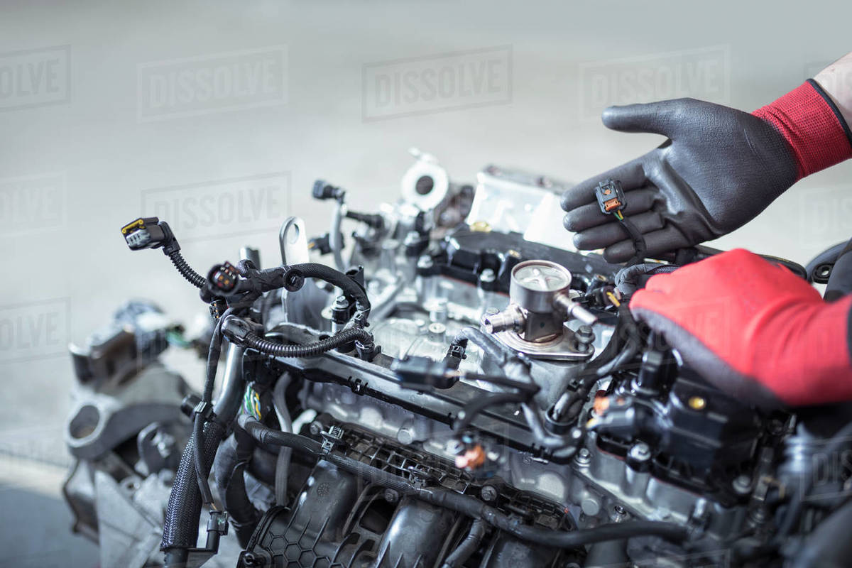Gloved hands with engine in car service centre Royalty-free stock photo