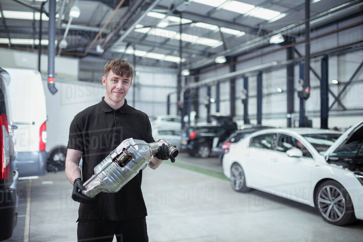 Portrait of apprentice engineer holding catalytic converter in car service centre Royalty-free stock photo