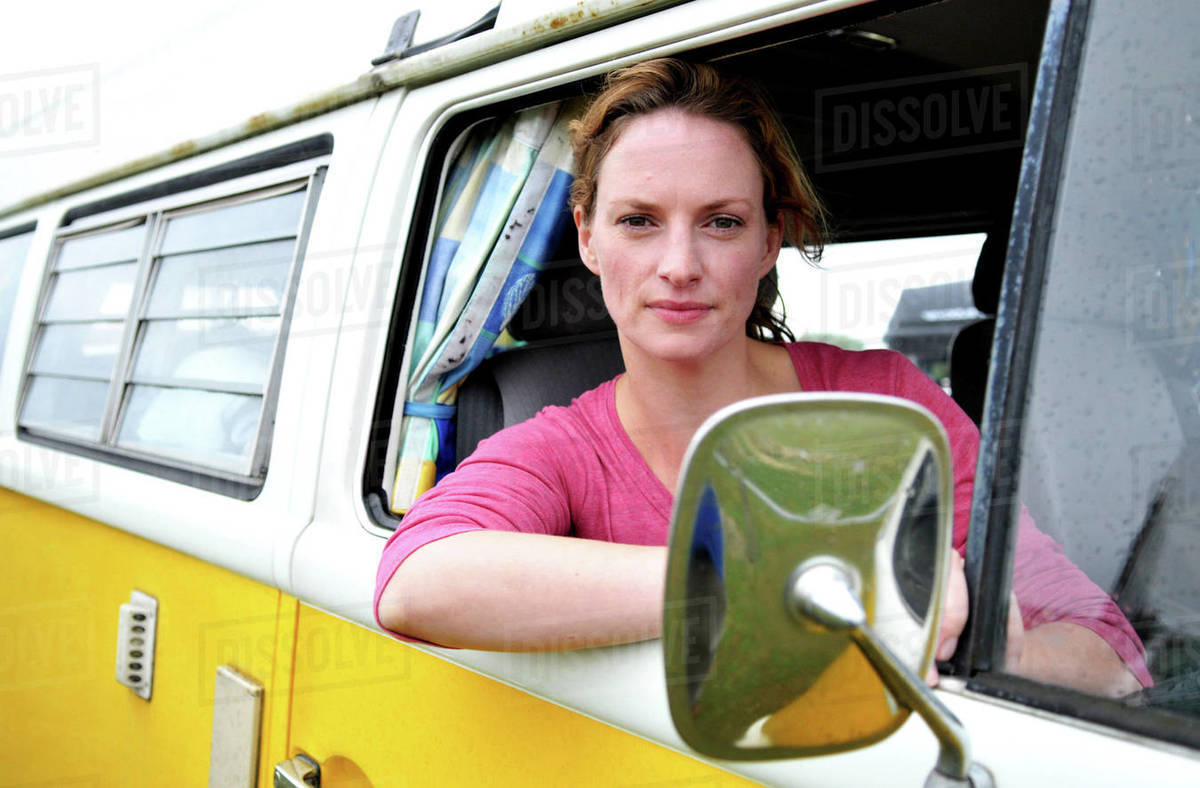 Mid adult woman looking out from camper van window, portrait Royalty-free stock photo