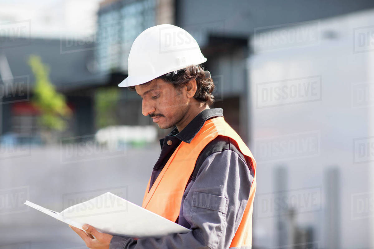 Male engineer looking at plans by industrial building Royalty-free stock photo