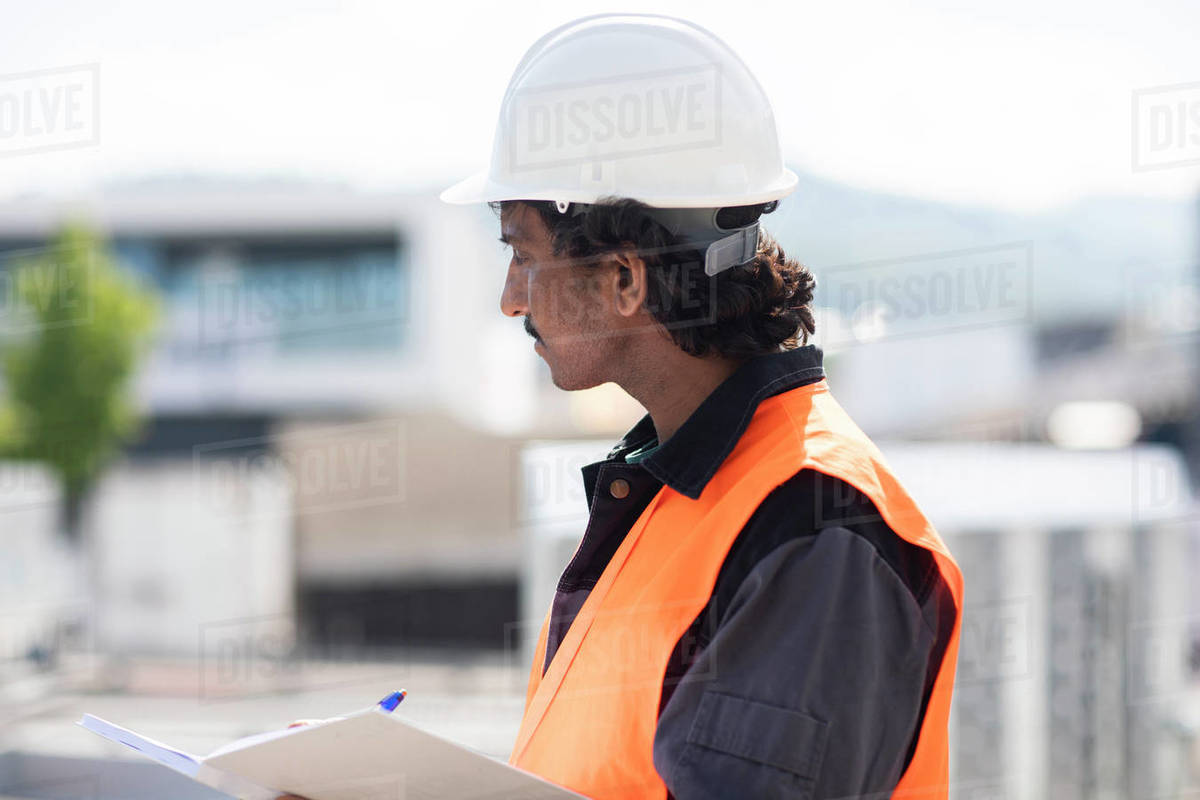 Male engineer outside industrial building writing in notebook, side view Royalty-free stock photo