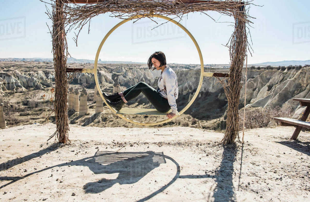 Woman playing on circular swing overlooking fairy chimney valley, Göreme, Cappadocia, Nevsehir, Turkey Royalty-free stock photo