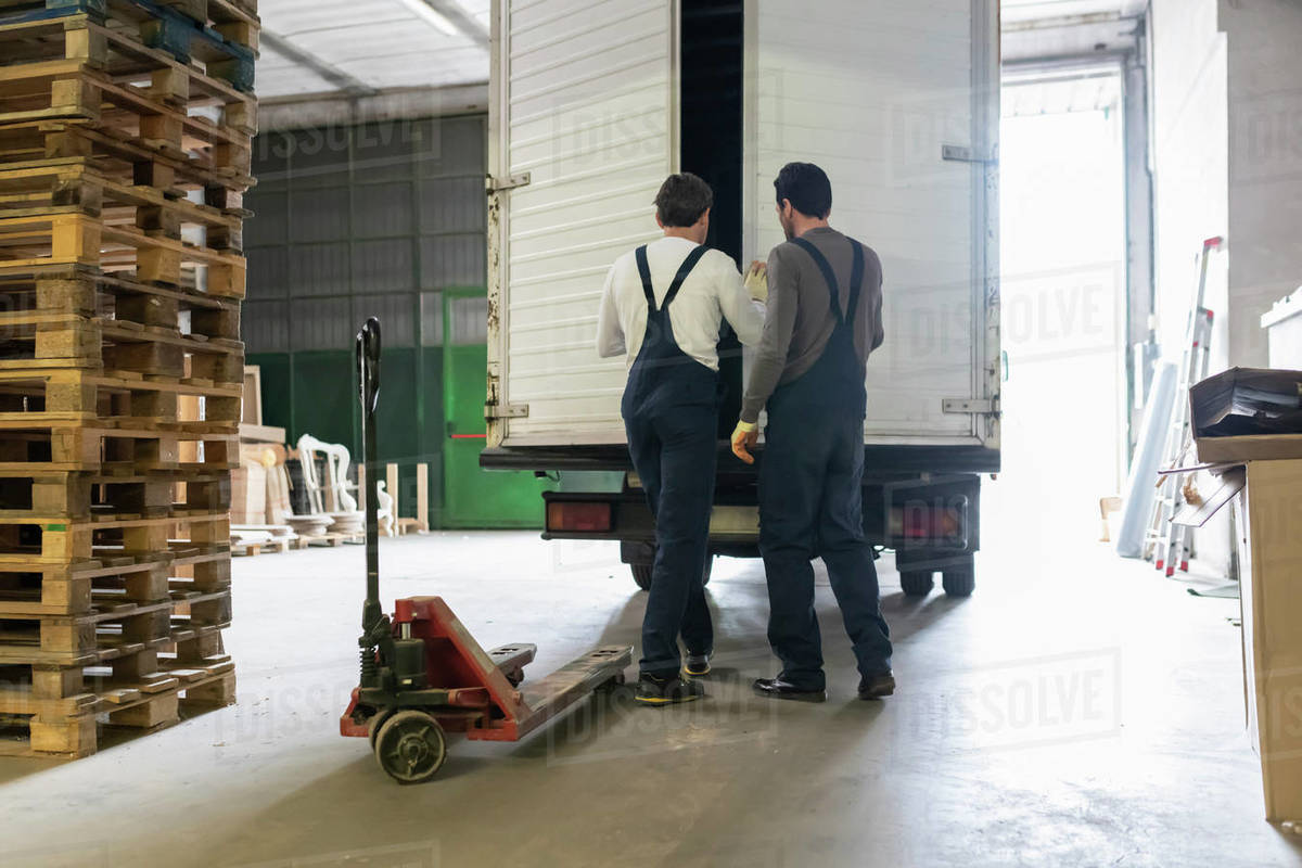 Workers closing door of truck in factory Royalty-free stock photo
