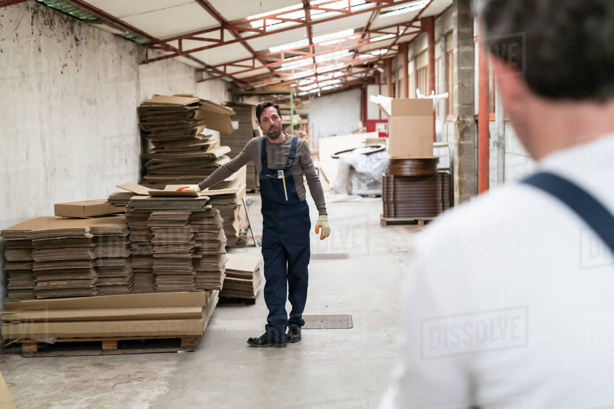 Worker resting hand on stack of cardboard boxes in factory Royalty-free stock photo