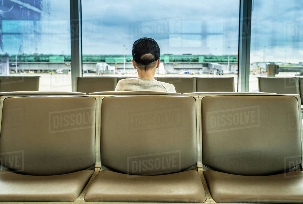 Teenage boy on seat looking out from airport departure lounge, rear view Royalty-free stock photo