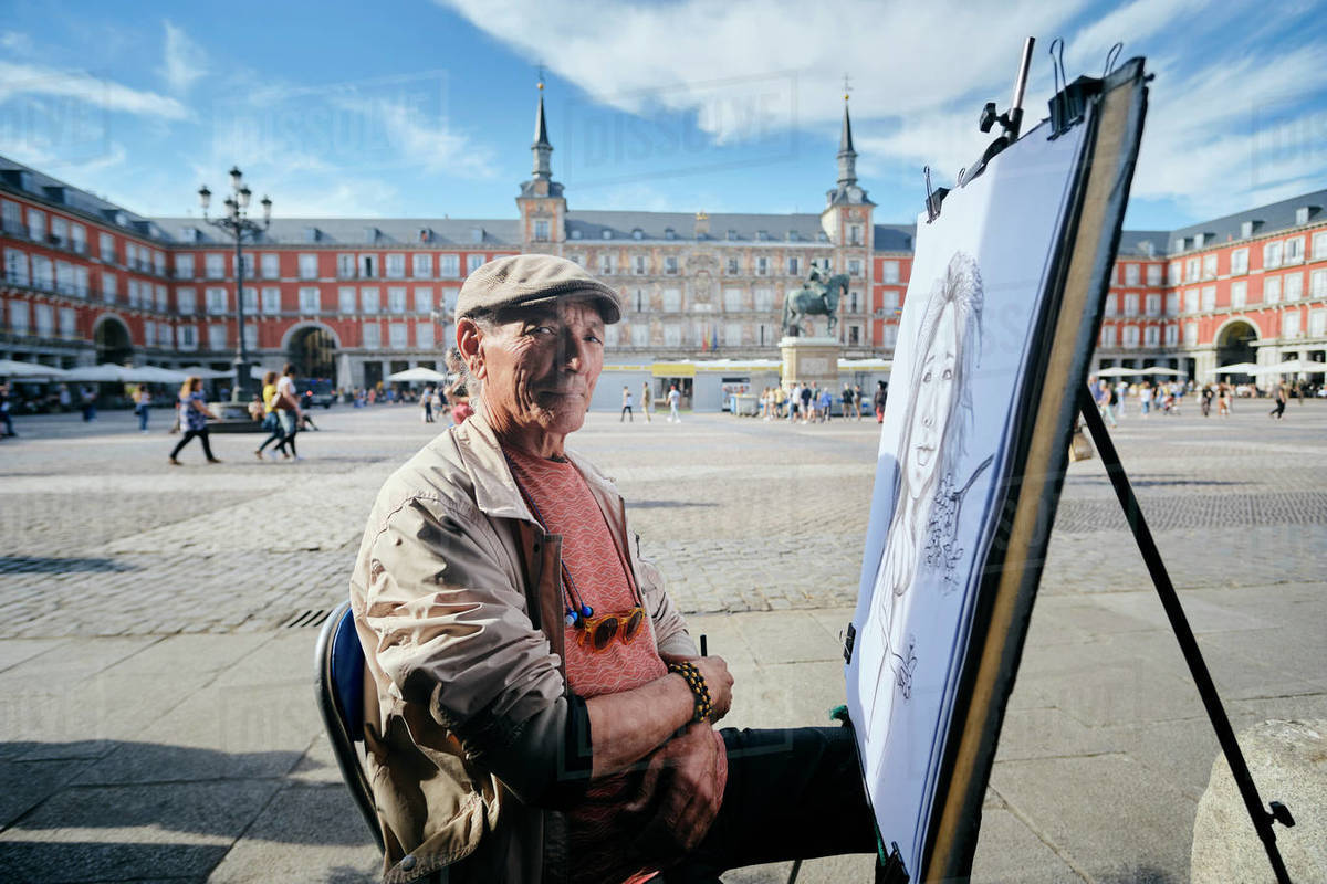 Mature male street artist by drawing canvas in town square, portrait, Madrid, Spain Royalty-free stock photo