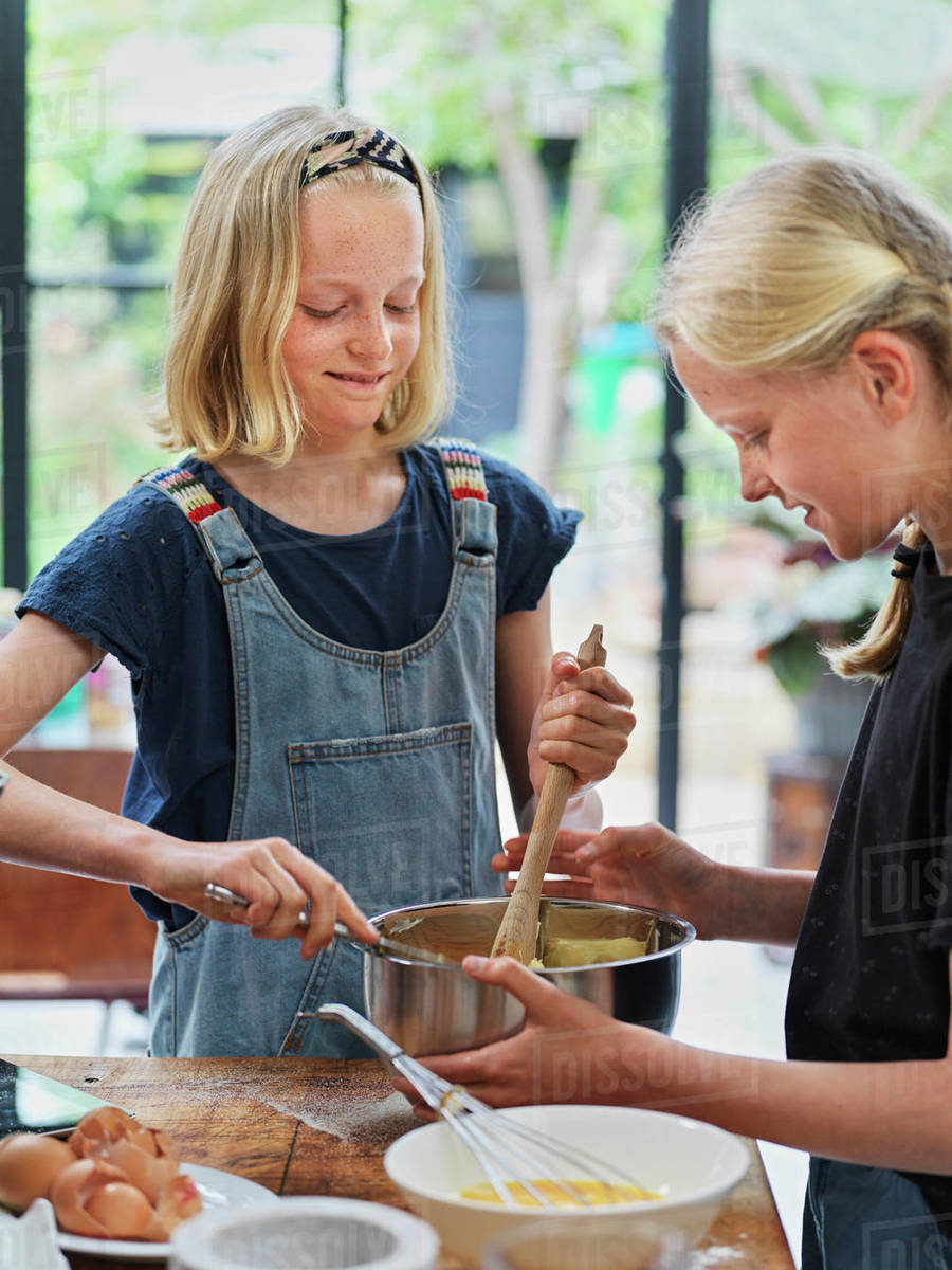 Girl and her sister baking a cake, stirring cake mixture in mixing bowl at kitchen table Royalty-free stock photo